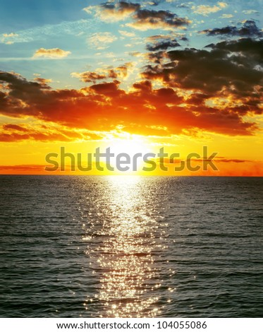 red sunset over water with waves - stock photo