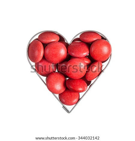 Red sweet beans in heart shaped frame isolated over white - stock photo