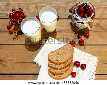 Red sweet cherries, bread slices on a white canvas napkin, eggs and yogurt on the wooden table. Summer composition in a rustic style - stock photo