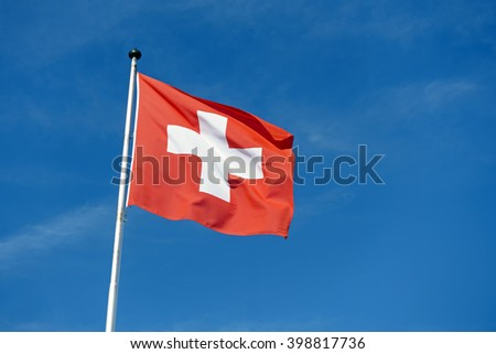 Red Switzerland national flag on pole waving against clear blue sky - stock photo