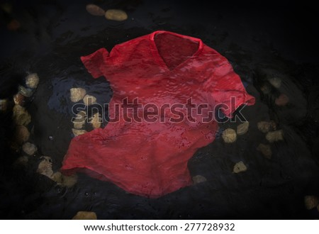 Red t-shirt floating or sinking in water - stock photo