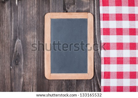 Red tablecloth, menu blackboard on wooden table background - stock photo