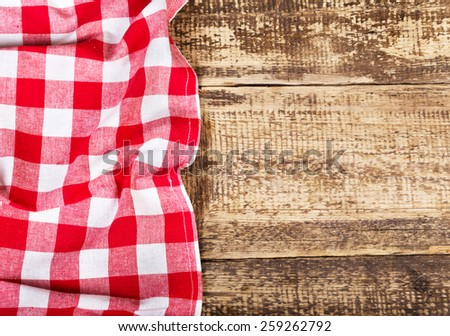 red tablecloth on old wooden table - stock photo