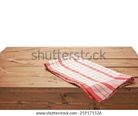 Red tablecloth or towel over the surface of a brown wooden table, composition isolated over the white background - stock photo