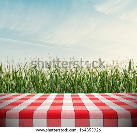 Red tablecloth template on cornfield and cloudy sky - stock photo