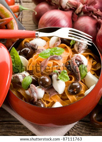 red tagliatelle with mozzarella, anchovies and black olives