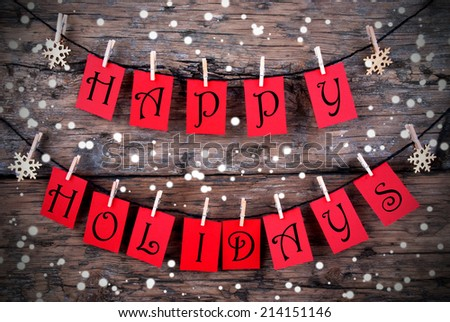 Red Tags with Happy Holidays on it Hanging on a Line on Wood with Snow, Christmas or Winter Holiday Greetings - stock photo