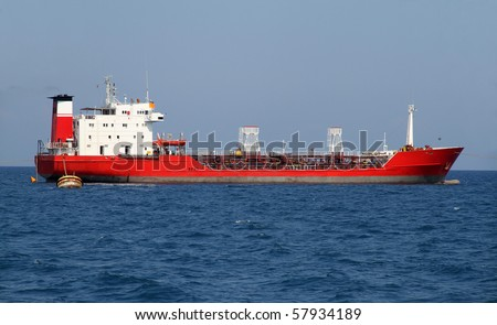 Red tanker designed for transporting crude oil is at anchor near the port - stock photo