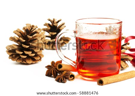 red tea in a glass, cinnamon sticks, star anise and some conifer cones on white background - stock photo
