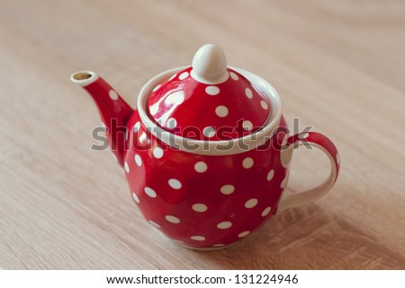 red teapot on the table - stock photo