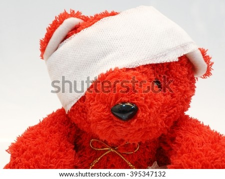 Red teddy bear with bandage over his head - stock photo
