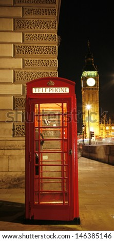 Red Telephone Booth at night, Big Ben in distance. Red phone booth is one of the most famous London icons.  - stock photo