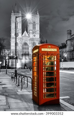Red telephone booth in front of Westminster Abbey, London, by night