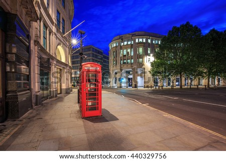 Red telephone box in street with  architecture in London at night. - stock photo