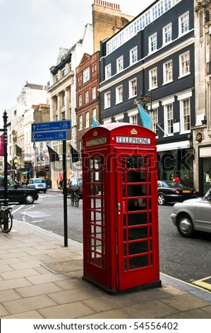 Red telephone box on busy London street in England - stock photo