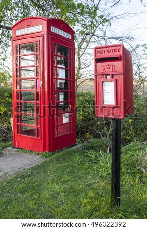 Red telephone box used as library with post box in front