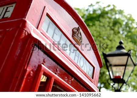 red telephone box with old fashioned london street light in soft focus - stock photo