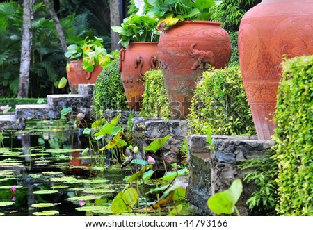 Red terracotta pottery between green plants and hedges above a water ditch