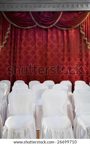 Red theater curtain and white chairs. Stage show presentation concept - stock photo