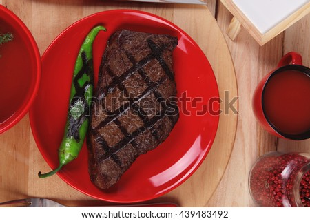 red theme lunch : fresh grilled bbq roast beef steak red plate green chili tomato soup ketchup sauce paprika small jug glass ground pepper american peppercorn modern cutlery served wooden plate table - stock photo