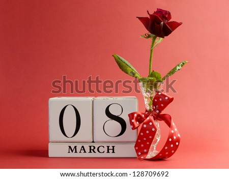 Red theme, save the date white block calendar for International Women's Day, March 8, decorated with flower, vase and polka dot ribbon.