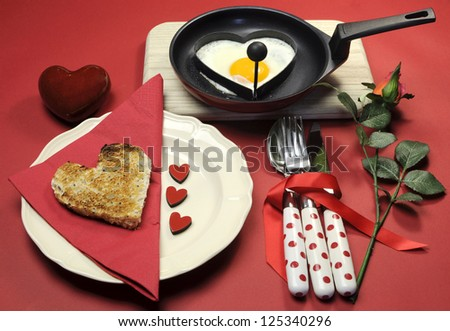 Red theme Valentine breakfast with heart shape egg and toast with love hearts on red background. - stock photo