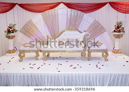 red themed wedding stage with gold trimmed benches - stock photo