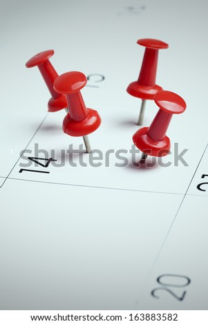 Red thumbtacks on calendar, Important date or meeting appointment reminder concept. Blue cast filter and copy space for text included. - stock photo