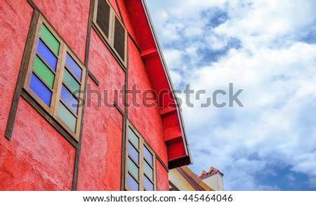 Red tile window and house roof  against blue sky. Image is vintage effect and low light photo