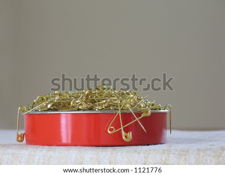 Red tin filled with gold pins