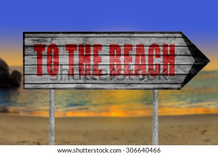 Red To The Beach wooden sign with on a beach background