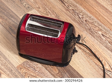 Red toaster on wooden background - stock photo