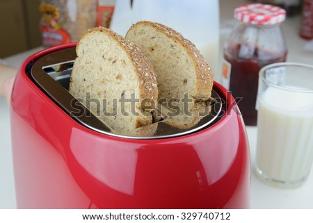 red toaster with two whole wheat in the pockets - stock photo