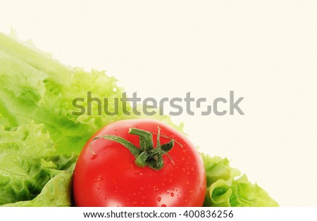 red tomato and  green salad isolated over white background