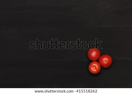 black table top view. red tomato on black table. wooden table top view. the are view o