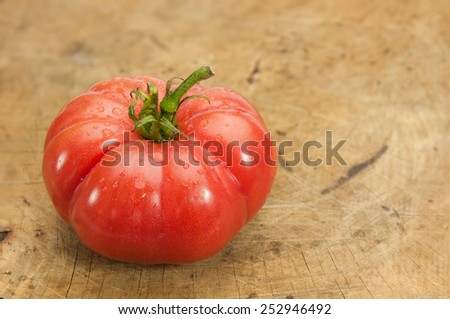 Red tomato on wooden table.
