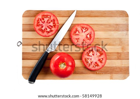 Red tomato slices and knife on chopping board - stock photo
