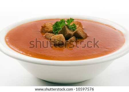 Red tomato soup on white background.  crests and chervil in the soup. - stock photo