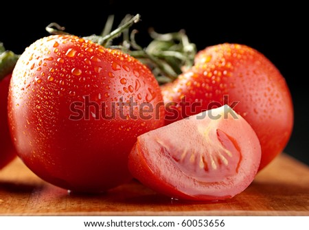 Red tomato with slice on wood board closeup - stock photo