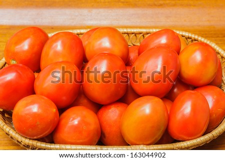 Red tomatoes in basket, rattan weaving multi-tenant placement.