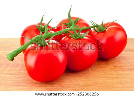 Red tomatoes on a branch on wooden board - stock photo
