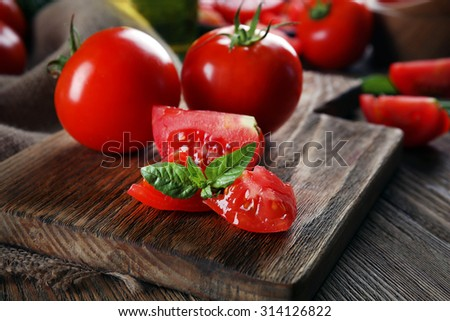 Red tomatoes on cutting board closeup - stock photo