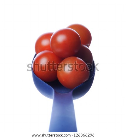 Red tomatoes on the spoon - stock photo
