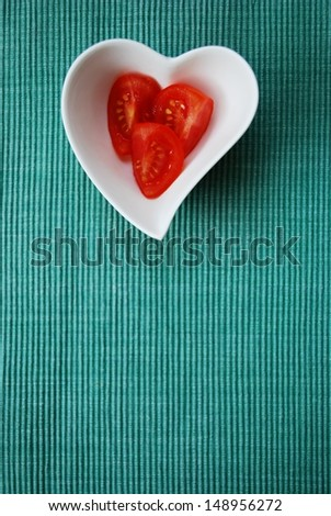 Red tomatoes salad in heart shape bowl on green background, free space for text - stock photo