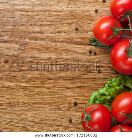 red tomatoes with green salad on wooden background