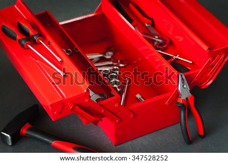 Red toolbox with metal work wrench kit of repairman. Pliers, hammer and many other chrome tools for automobile repair on workshop background - stock photo
