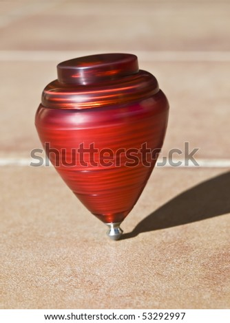 Red top spinning on its axis. Vertical composition - stock photo
