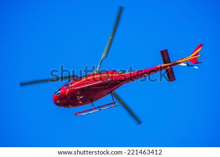 Red Tour Helicopter on the Clear Sky. Red Chopper Flying Over Head. - stock photo