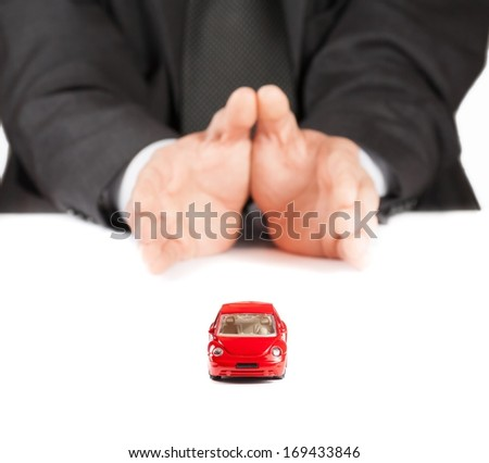 red toy car in front of businessman on white table, concept for insurance, buying, renting, fuel or service and repair costs - stock photo