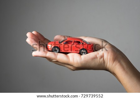 Red toy car in woman hand.